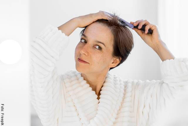 Foto de una mujer aplicándose un tratamiento capilar para ilustrar ¿cómo engrosar el cabello con mascarilla de mostaza?