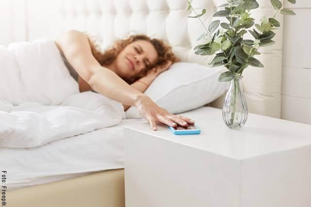 Foto de una mujer tomando su celular desde la cama