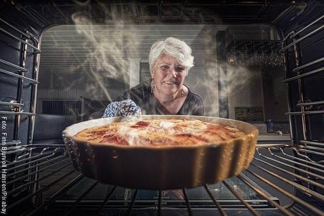Foto de una mujer poniendo una refractaria en el horno para ilustrar cómo hacer torta de banano