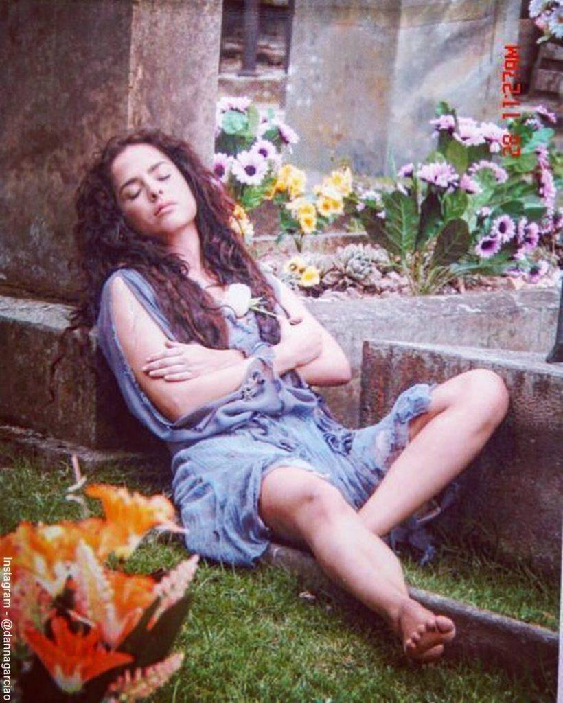 Foto de Danna García acostada en una tumba interpretando a Bella calamidades