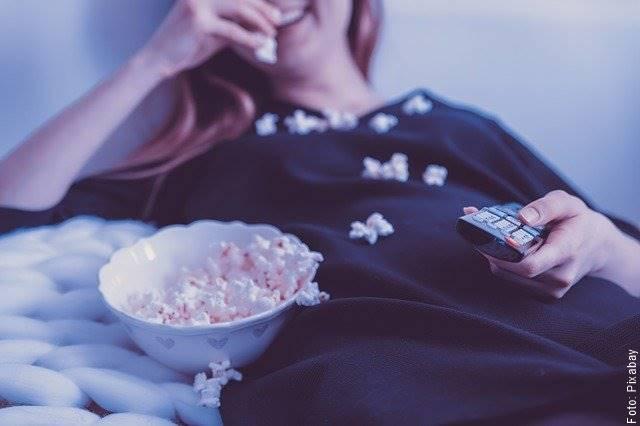 Foto de una mujer comiendo maíz pira y viendo televisión
