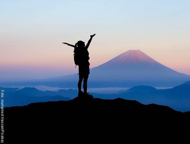 Foto de una mujer en la cima de una montaña