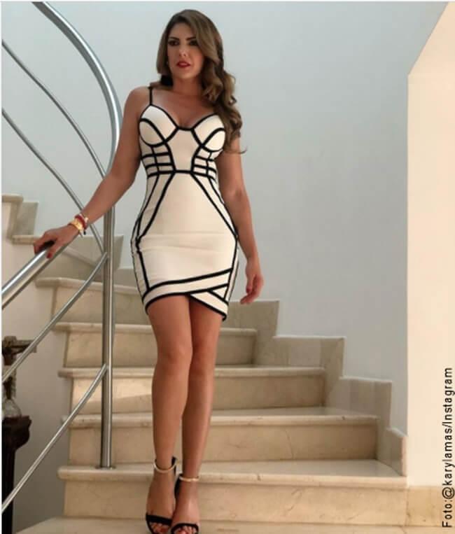 Foto de Ana Karina Soto con vestido elegante blanco bajando las escaleras