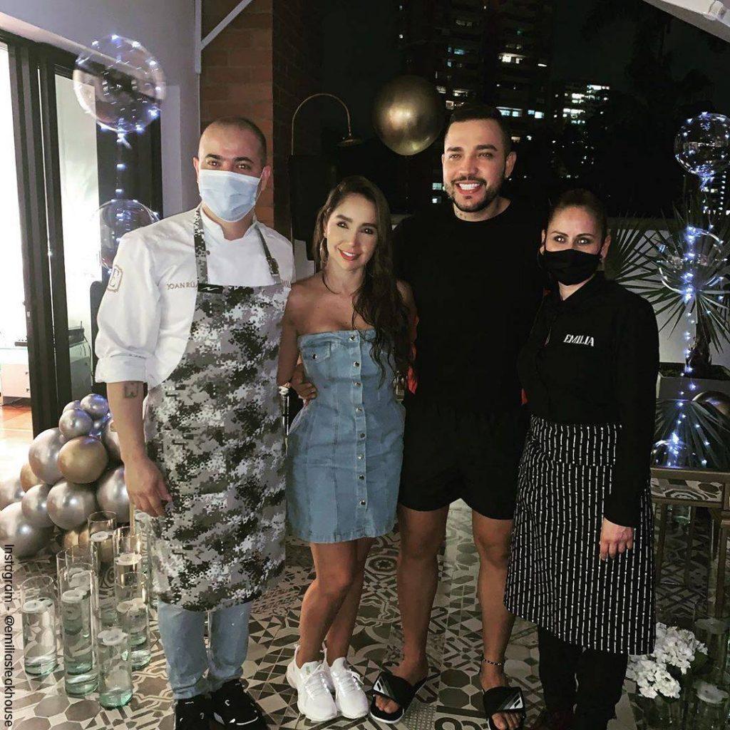 Foto de Jessi Uribe y Paola Jara al lado de los cocineros de Emilia Steakhouse