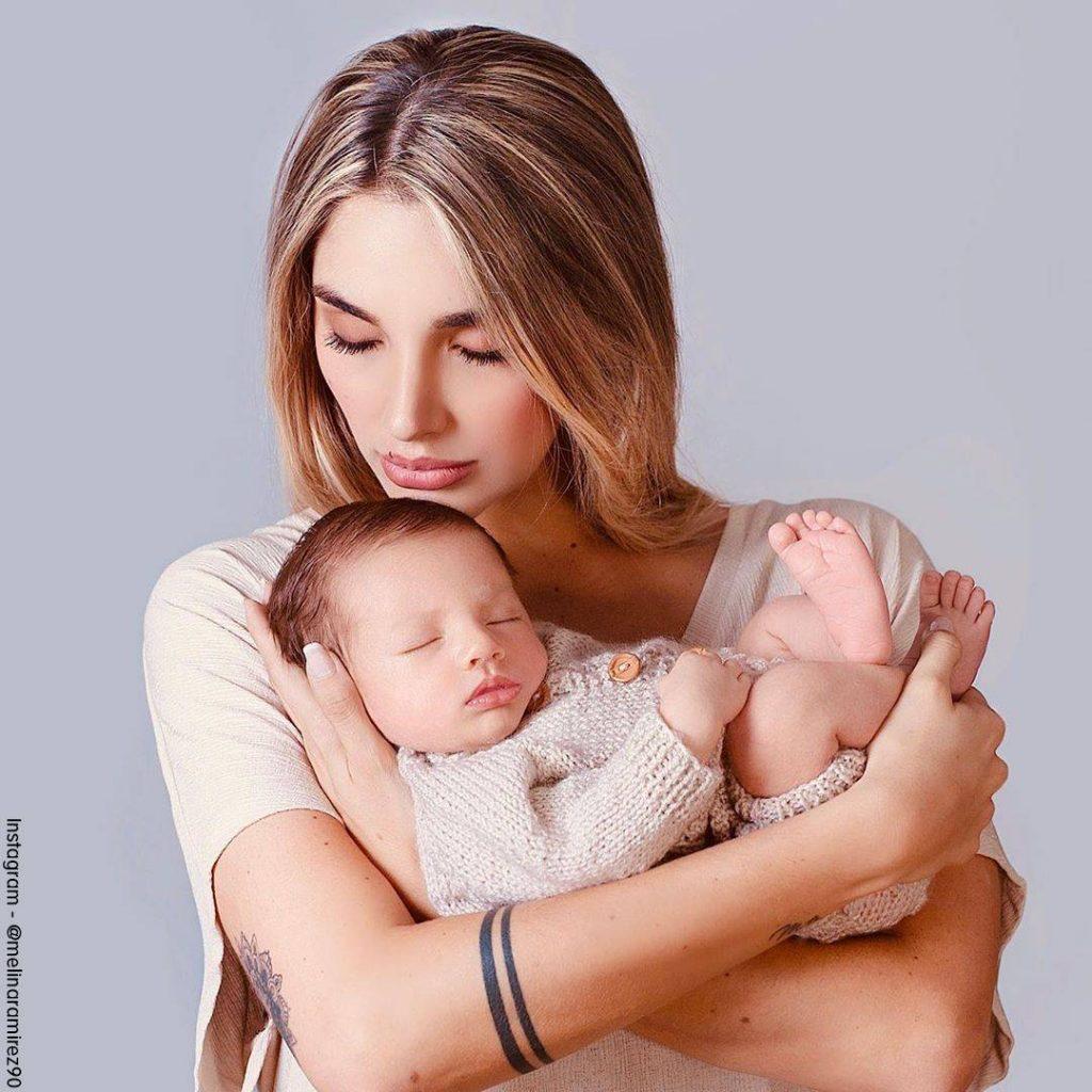 Foto de Melina Ramírez con un tatuaje en su brazo y abrazando a su bebé