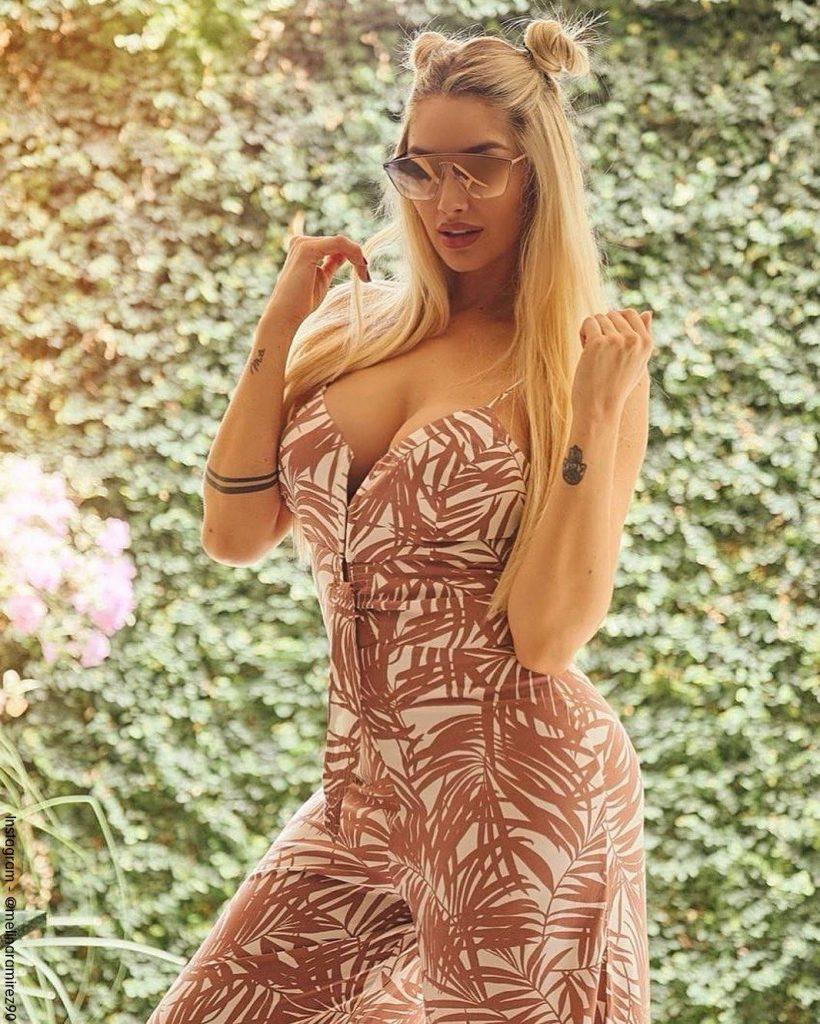 Foto de Melina Ramírez con un vestido de flores y luciendo su tatuaje en el brazo