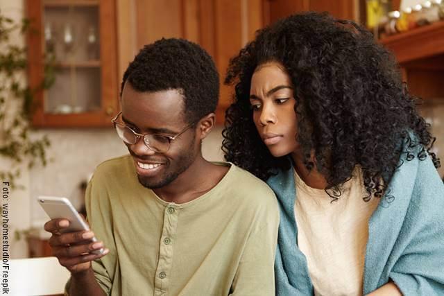 Foto de una pareja y la mujer mira el celular del hombre