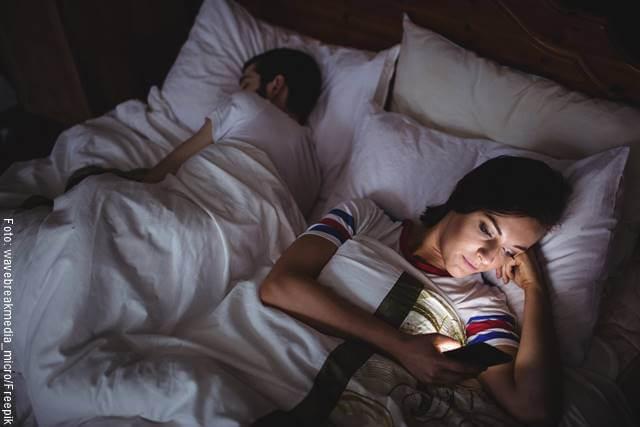 Foto de una pareja en la cama y la mujer mira su celular a escondidas