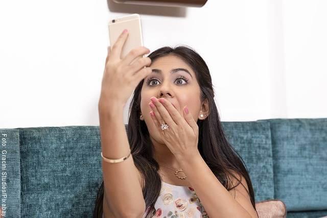 Mujer tomándose una foto y tapándose la boca