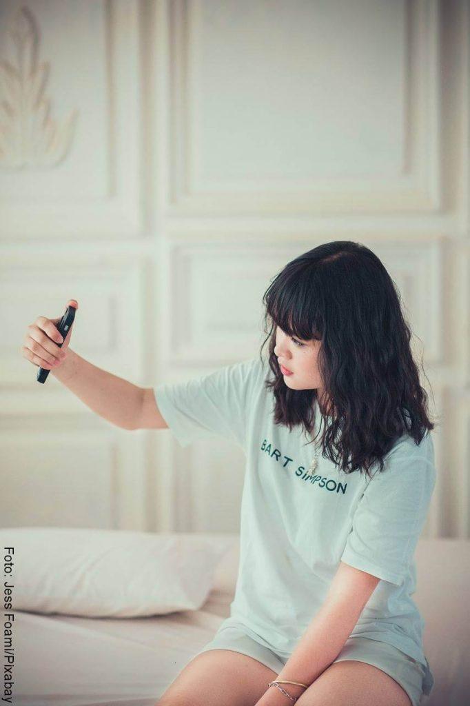 Mujer tomándose una foto sobre la cama