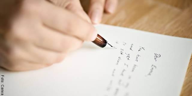 Foto de la mano de una mujer escribiendo una carta