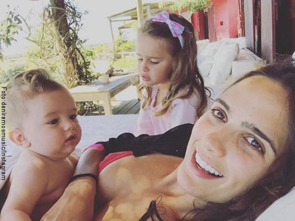 Daniela Ramos con sus hijos recostada en un sofá