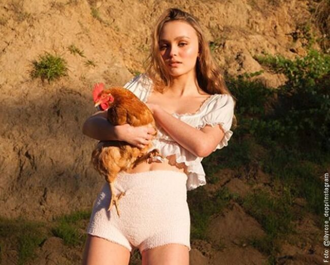 Hija de Jonny Deep con una gallina en sus manos
