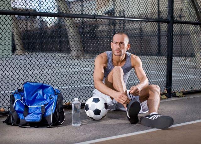 Foto de un hombre amarrándose los zapatos junto a un balón de fútbol