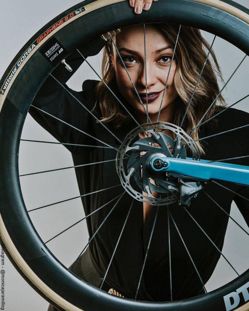 Foto de Mónica Jaramillo sosteniendo una rueda de una bicicleta de carreras