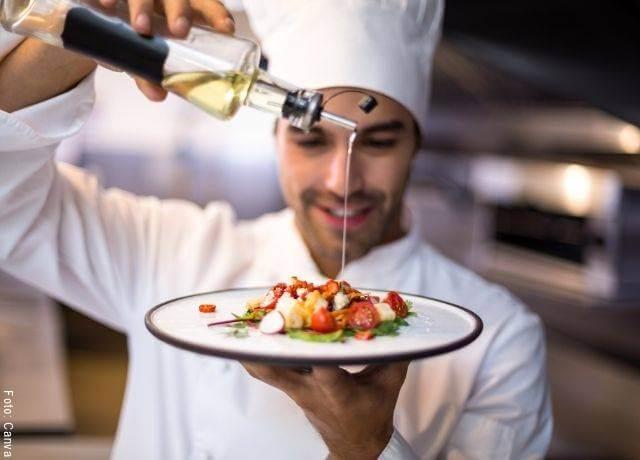 Foto de un chef poniendo aceite de oliva a un plato