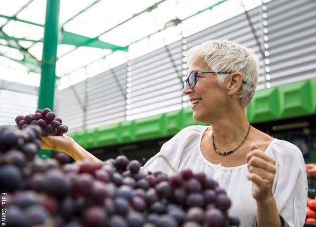 Foto de mujer comprando uvas