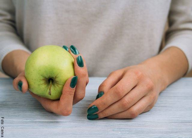 Foto de las manos de una mujer con una manzana