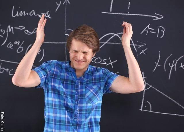 Foto de un joven confundido con las matemáticas con un tablero de fondo