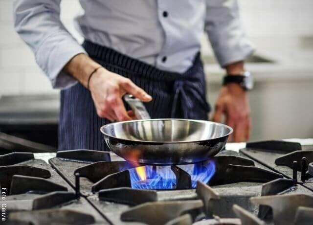 Foto de una persona con un sartén en el fuego