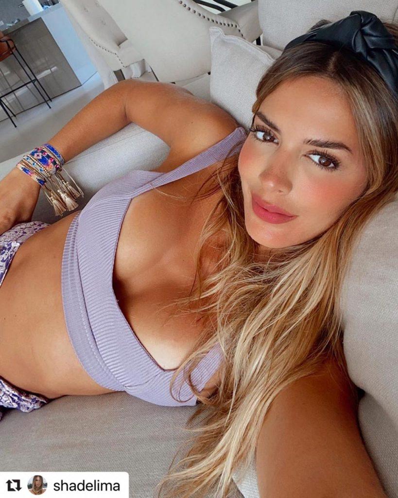 Shannon de Lima en top recostada en el sofá de su casa.