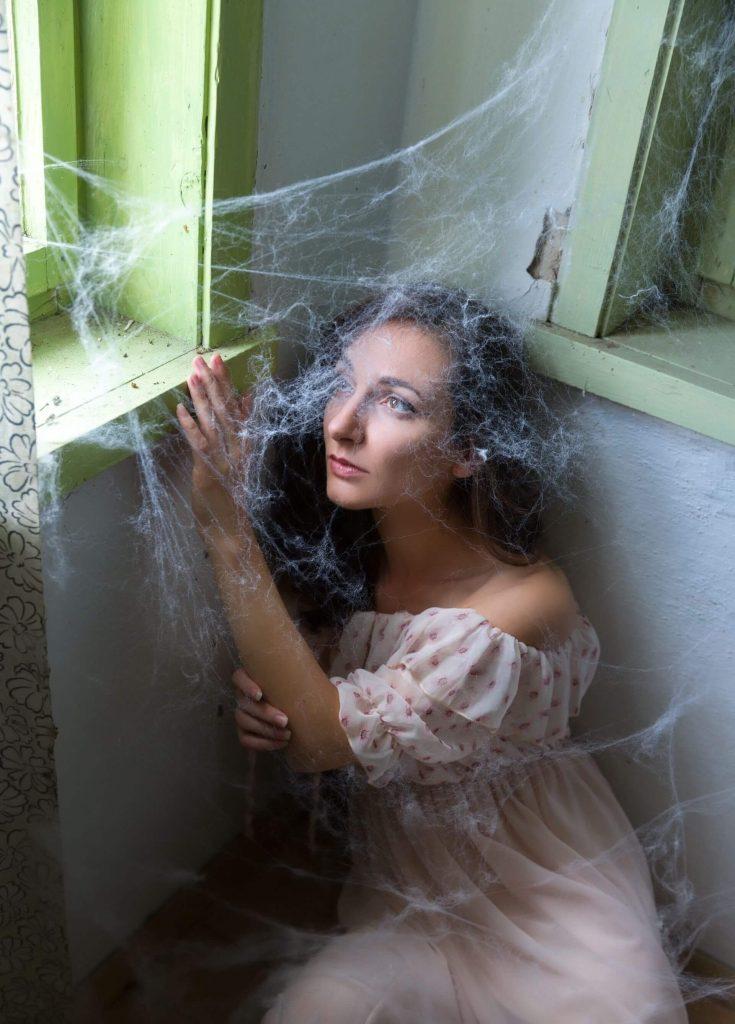 Foto de una mujer en su casa rodeada de telarañas