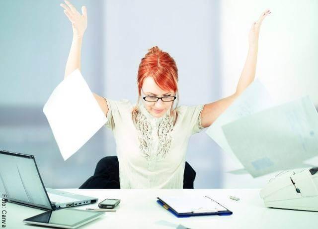 Foto de una mujer en su escritorio del trabajo y tirando papeles