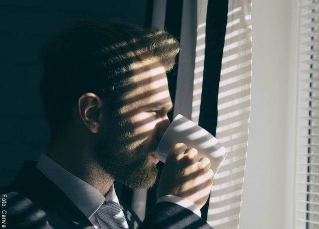 Foto de un hombre tomando café y mirando por la ventana