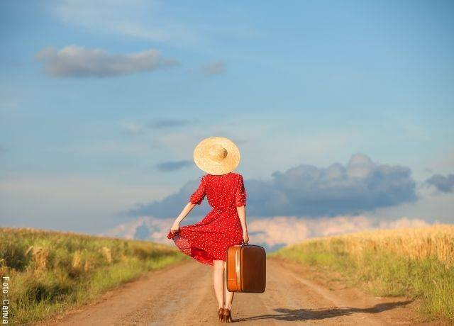 Foto de una mujer caminando con una maleta en la mano