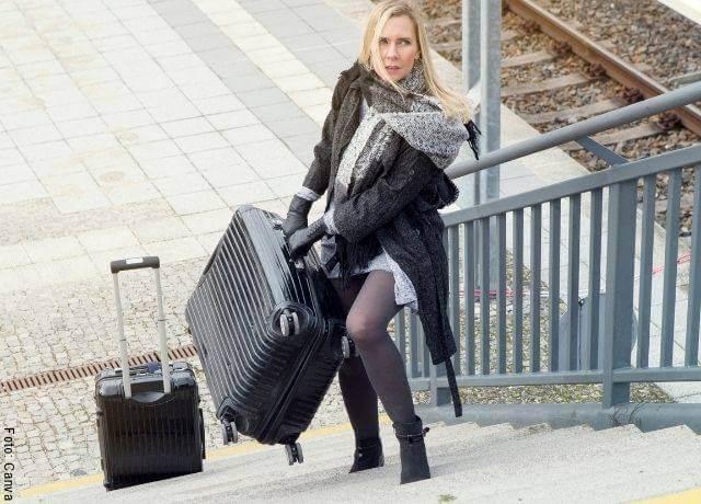 Foto de una mujer arrastrando una maleta negra