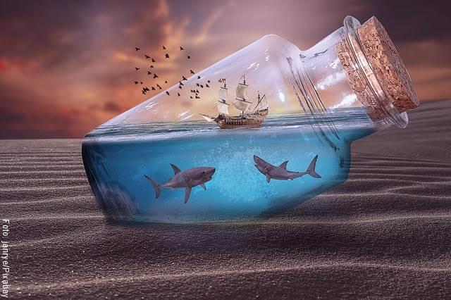 Foto de tiburones en un frasco con barco miniatura