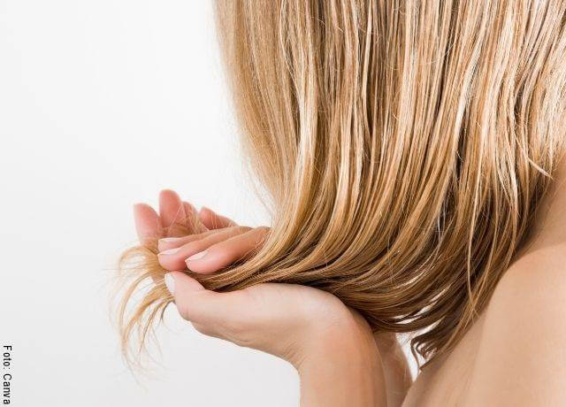 Foto del cabello de una mujer con un mechón en su mano