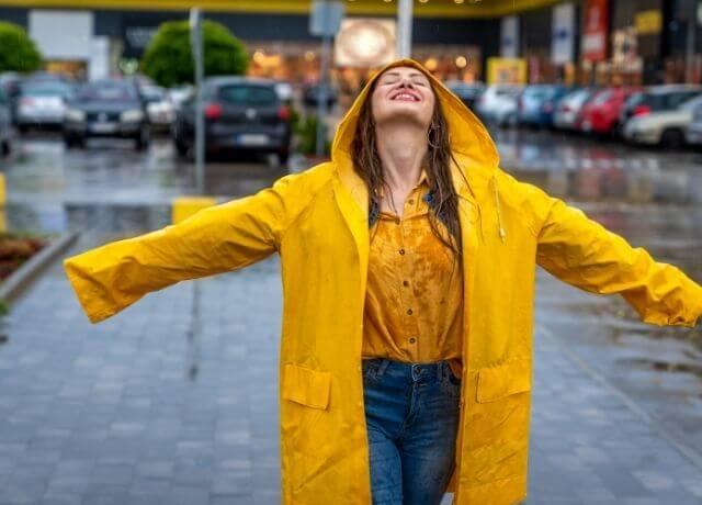 Foto de una mujer feliz bajo la lluvia
