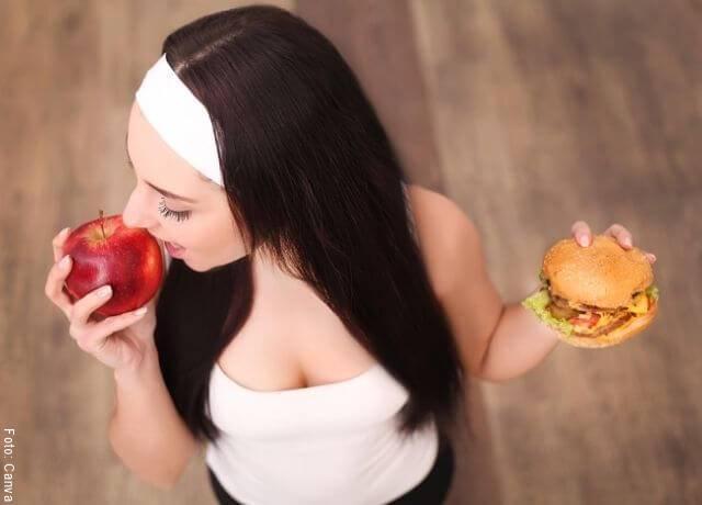 Foto de una mujer con una manzana y una hamburguesa
