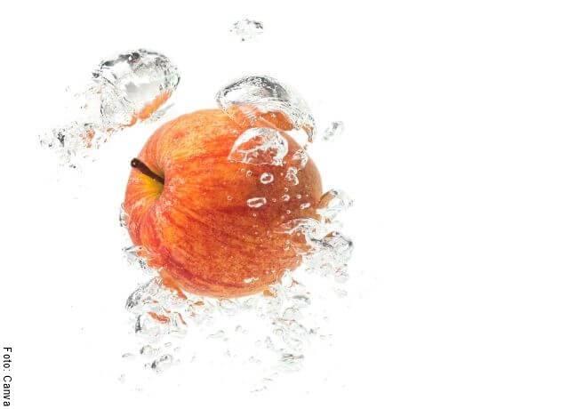 Foto de una manzana flotando en el agua para ejemplificar los beneficios de la manzana