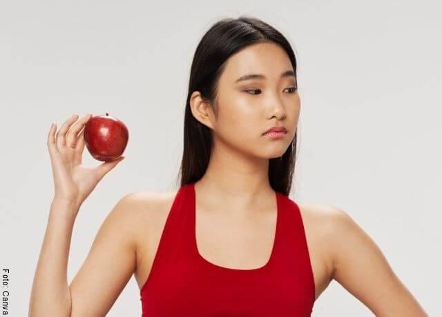 Foto de una mujer con una fruta en la mano