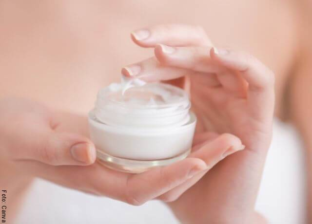 Foto las manos de una mujer con recipiente de crema facial en ellas