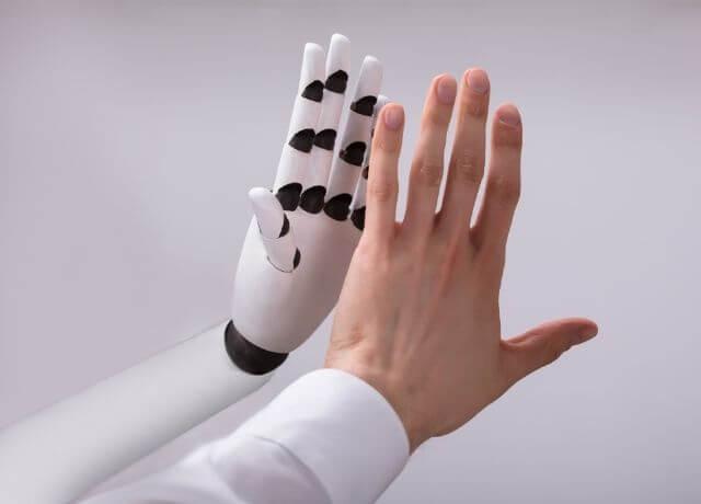 Foto de una mano chocando la mano de un robot
