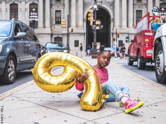 Foto de una niña con un globo en forma de 9