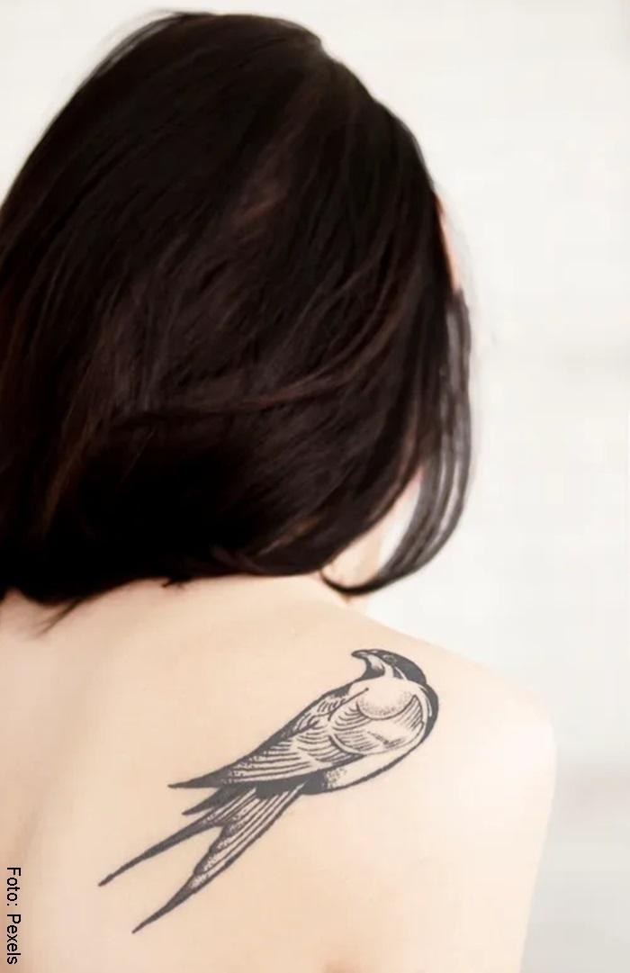 Mujer con tatuaje de un ave en la espalda