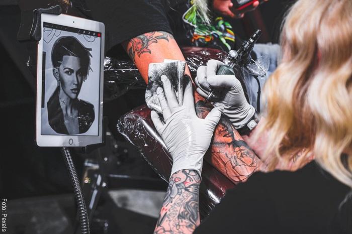 Foto de una mujer haciendo un tatuaje