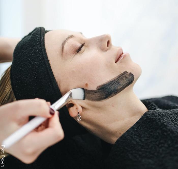 Foto de mujer aplicando mascarilla de carbón activado de manera correcta