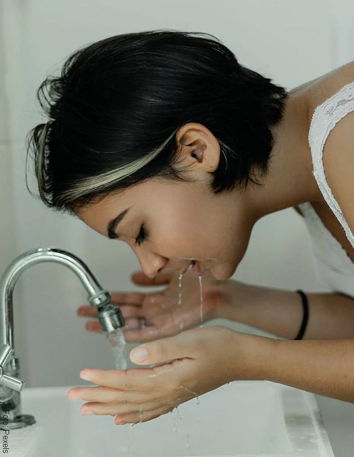 Foto de mujer lavando su rostro