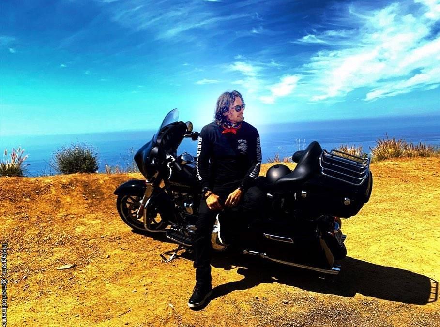 Foto de Mario Cimarro junto a su moto en un lugar de California