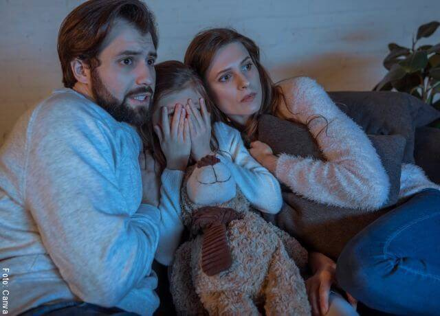 Foto de una pareja y su hija viendo una película de terror
