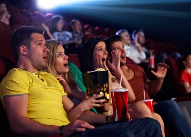 Foto de personas asustadas viendo una película de terror en cine