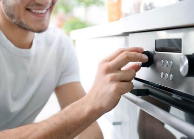 Foto de un hombre encendiendo el horno