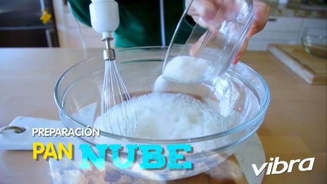 Foto de un recipiente en el que se están batiendo claras de huevo y le vierten azúcar