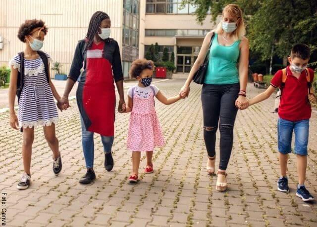 Foto de varios niños con una señora saliendo de un colegio
