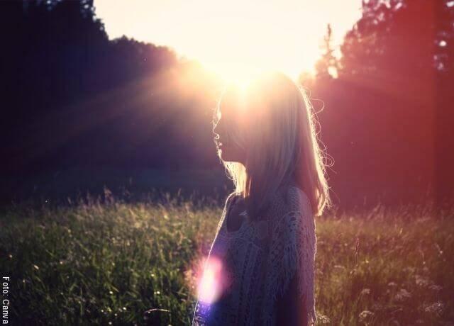 Foto de una mujer con el sol de fondo